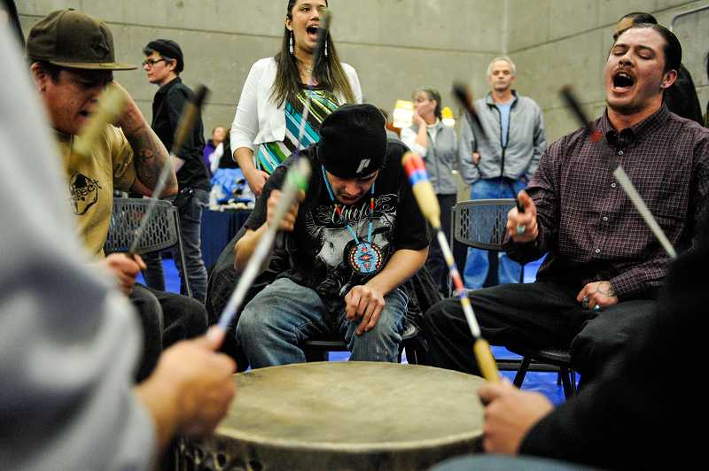 by: TIMES PHOTO: JOHN LARIVIERE - Members of Wy'East drum group, from left, Wallace Deerskin, Steven Paul and Russell Charley drum and sing during the grand entry of dancers.