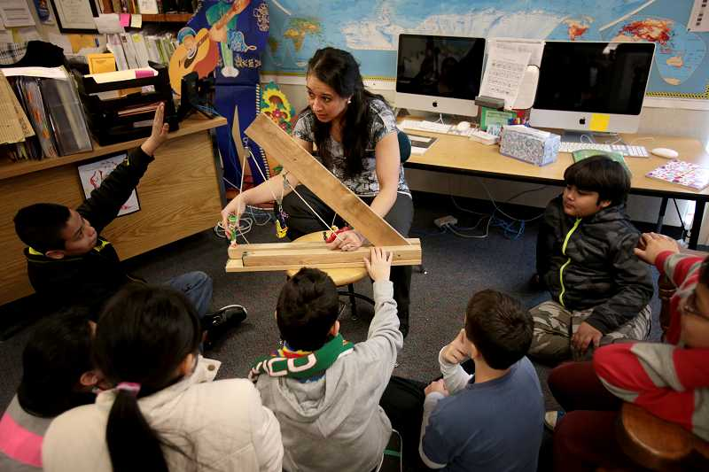 by: TIMES PHOTO: JONATHAN HOUSE - Deer Creek Elementary School teacher Maria Copelan shows her 5th grade English Language Learners class how a pulley system works.