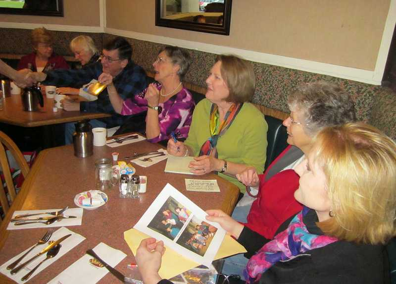 by: GAZETTE PHOTO: BARBARA SHERMAN - Sharing photos is part of the fun of the monthly reunions for (from left) Leone Forseth, Lolly and Scott Peavy, Chris Lang, Pam Woltze, Linda Abercrombie and Leanne Duckering.