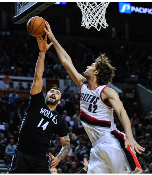 Trail Blazers center Robin Lopez gets a piece of a shot by Minnesota post Nikola Pekovic.