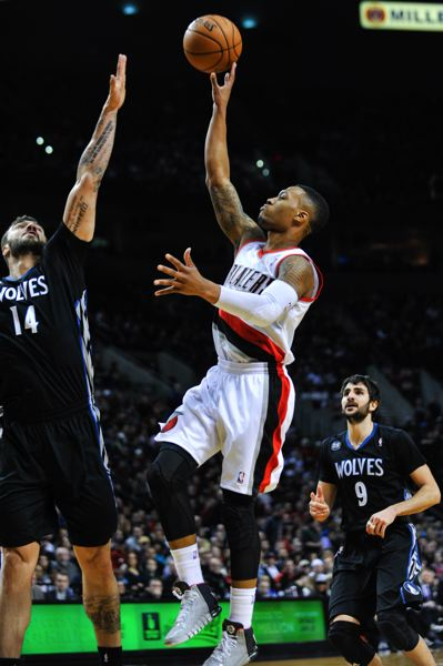 Blazers guard Damian Lillard launches a floater over Minnesota big man Nikola Pekovic.
