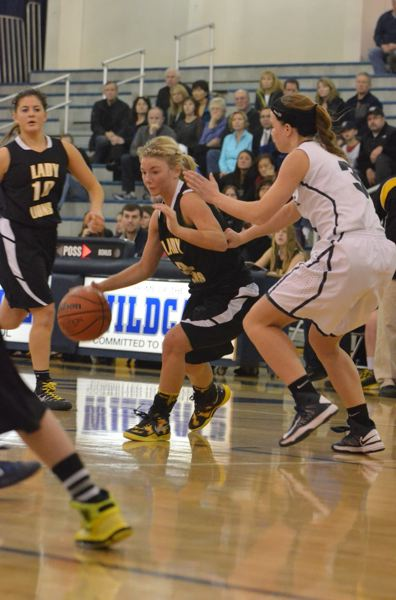 by: JEFF GOODMAN - Senior Nicole Harcourt drives around a Wildcat defender during the Lions' visit to Wilsonville on Jan. 24.