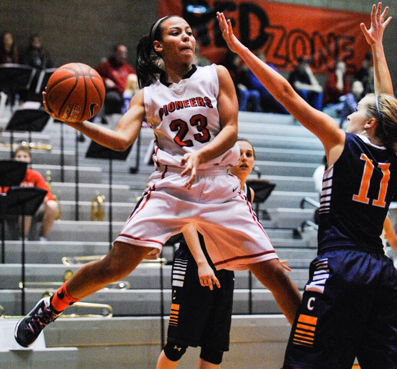 by: JOHN LARIVIERE - Senior guard Toria Bradford (23) dishes off to a teammate in Fridays game with Canby. Crisp passes and unselfish team play helped the Pioneers take control of the game early on.