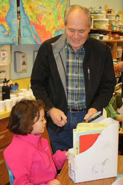 by: PEGGY SAVAGE - Don Sether hands out a dictionary to a third-grader at Rural Dell Elementary School.