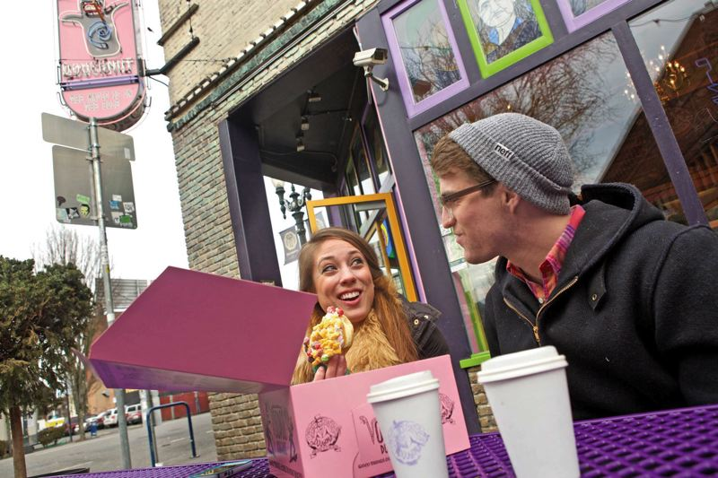 by: TRIBUNE PHOTO: JAIME VALDEZ - Annemarie Slaven and David Riott munch on Voodoo doughnuts after waiting in line on a chilly day to visit the popular shop.