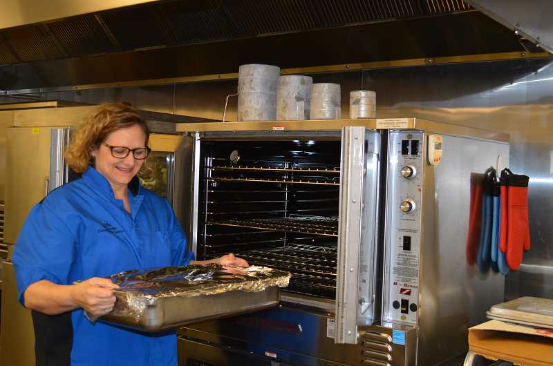 by: SUBMITTED PHOTO - Community center staff and participants thank the employees of Xerox and a private donor in Wilsonville for making the purchase of a new convection oven possible.