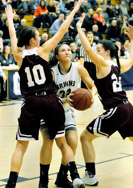 by: SETH GORDON - Hemmed in - Megan Arnoldy attempts to split a pair of Puget Sound players during GFU's 70-58 win over Puget Sound Saturday at Miller Gym. The Bruins now sit in second place in the NWC, one game behind unbeaten Whitman.