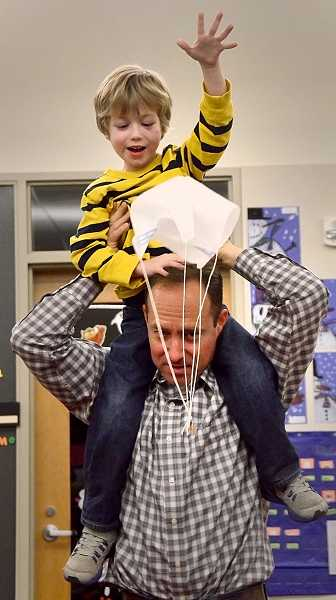 by: TIDINGS PHOTO: VERN UYETAKE - Kindergartener Chase Herbert has fun with the parachute he constructed with his dad, Brad Herbert.