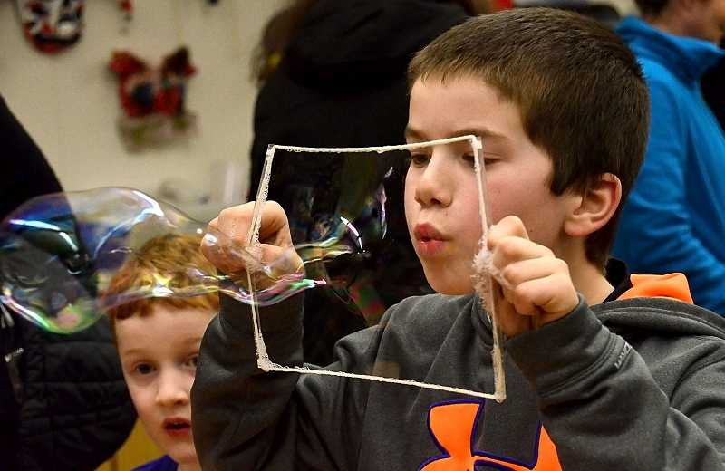 by: TIDINGS PHOTO: VERN UYETAKE - Third-grader Kael Loun blows giant bubbles at Trillium's Family STEM night Jan. 16.