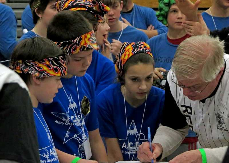 by: SUBMITTED PHOTO - Three members of ACES confer with a judge during the Lego Robotics tournament Jan. 18. From left, Justin LeBlanc, Michael Talbert and Emily Ivany.