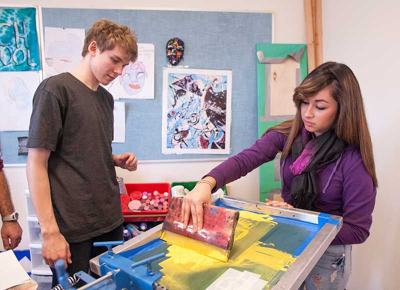 by: PAMPLIN MEDIA GROUP: JOSH KULLA - ATHS senior Sascha Ellis watches as junior Esthela Rodriguez uses screen-printing equipment on a T-shirt.