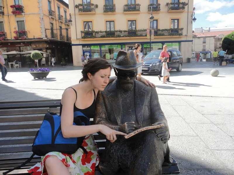 by: SUBMITTED PHOTO - Passing through Salamanca, Spain, during a European backpacking trip in 2010, Melissa Wilk paused to give a statue a few reading tips.