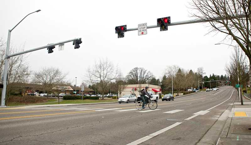 by: TIMES PHOTO: JAIME VALDEZ - Phillip Conroy, who recently moved to Beaverton from Norfolk, Va., rides his bike across the Fanno Creek Trail crossing on Southwest Hall Boulevard. Conroy used the crosswalk for the first time on Tuesday afternoon.