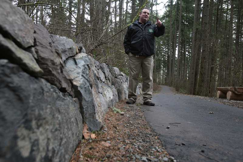 by: TIMES PHOTO: JONATHAN HOUSE - Matt Kilmartin, Tualatin Hills Park and Recreation District project manager for the Lowami Hart Woods Natural Area, stands in front of a handmade stone wall along one of its newly surfaced trails.