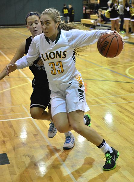 by: VERN UYETAKE - Sidney Kolasinski drives past Lakeridge's Colleen Ellis in the Lions' win over the Pacers.
