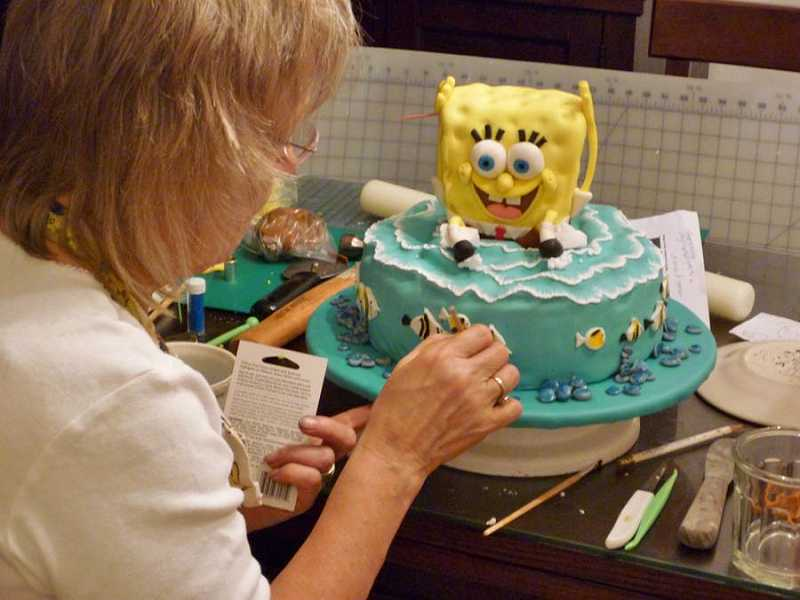 by: COURTESY OF SANDI NELSON - LONG HOURS LEAD TO FUN RESULTS - Sandi Nelson puts the finishing touches on a Sponge Bob cake designated for one of her lucky grandchildren.