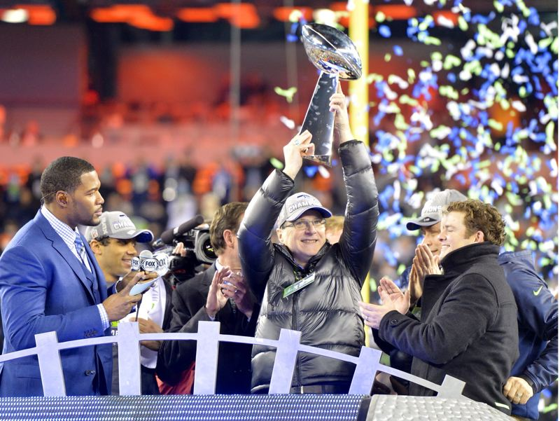 by: COURTESY OF MICHAEL WORKMAN - Paul Allen, Seattle Seahawks owner, hoists the Vince Lombardi Trophy after his team's 43-8 Super Bowl XLVIII triumph over the Denver Broncos.