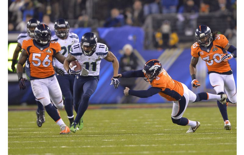 by: COURTESY OF MICHAEL WORKMAN - Seattle's Percy Harvin finds a hole on his way through the Denver kickoff team and begins the second half with an 87-yard touchdown return.