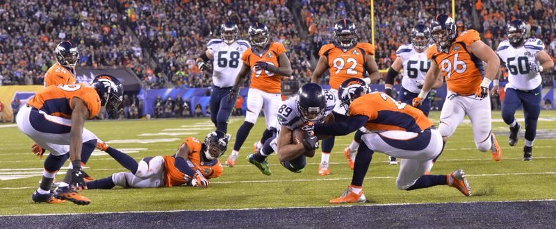 by: COURTESY OF MICHAEL WORKMAN - Receiver Doug Baldwin dives across the goal line for a Seattle touchdown.