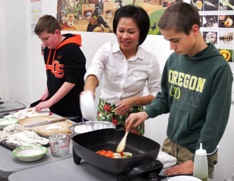 by: OUTLOOK PHOTO: JIM CLARK - (Left) Derrick Tomlinson, 14, and Max Kuchuryan,14, (right), help Nang Dunn (center) make the Lao chicken noodle soup.