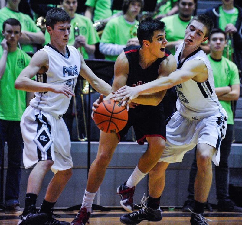 by: JOHN LARIVIERE - Oregon City defenders Briggs Young (left) and Austin DeWitz (right) pressure Clackamas senior wing Andrew Gutwig during last weeks game with the Cavaliers. Gutwig hit five 3-pointers and scored 22 points to lead the Cavaliers in a 53-47 come-from-behind victory.