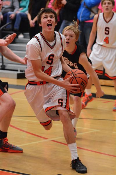 by: JOHN WILLIAM HOWARD - Indian sophomore Brennen McNabb drives to the basket for his only bucket of the game. Scappoose has won their last three league contests after dropping the opener to Tillamook.