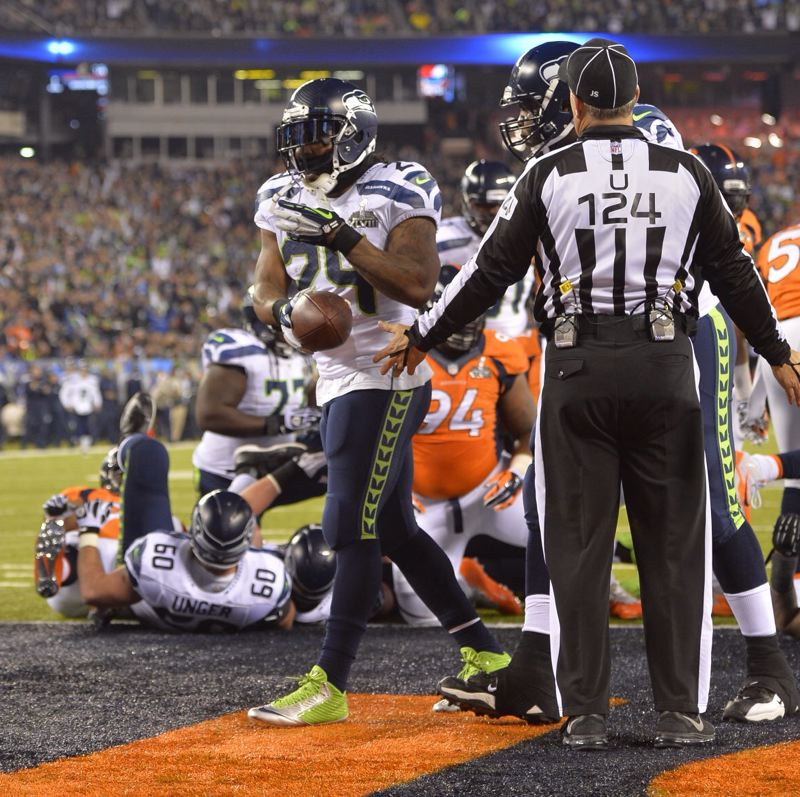Marshawn Lycnh hands the ball to the umpire his touchdown in Super Bowl LXVIII.