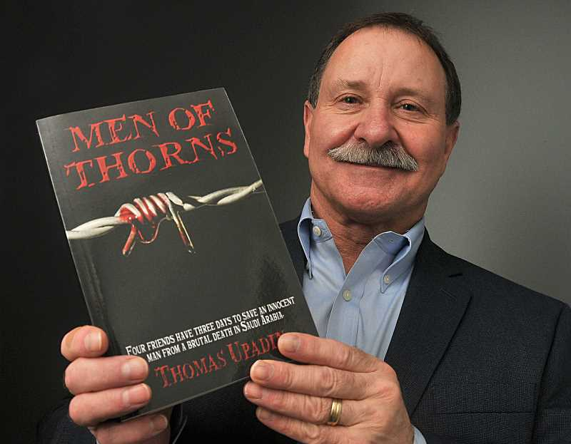 by: STAFF PHOTO: VERN UYETAKE - Tom Riddle holds a copy of his novel Men of Thorns. He writes under the pen name of Thomas Upadin.