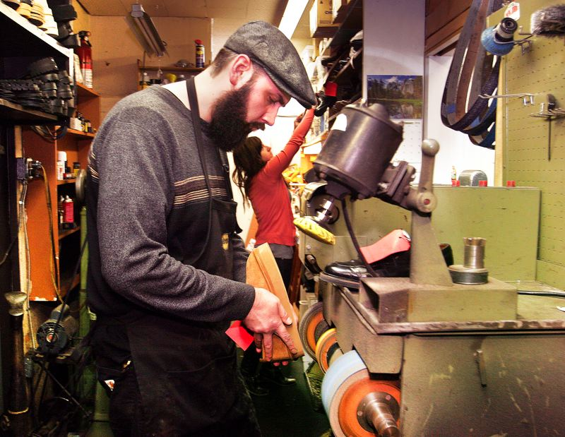 by: OUTLOOK PHOTO: JIM CLARK - Shoe repairman Gene Norman has been working at his trade for 15 years. He and his wife, Megan Sanford, seen in the background, have operated Gresham Shoe Repair for four years.