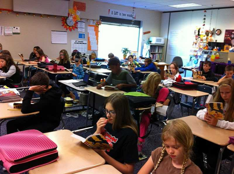 by: SUBMITTED PHOTO - Students in Dana VanderZandens sixth-grade class spend some class time reading this years selection for the Wood Reads program.