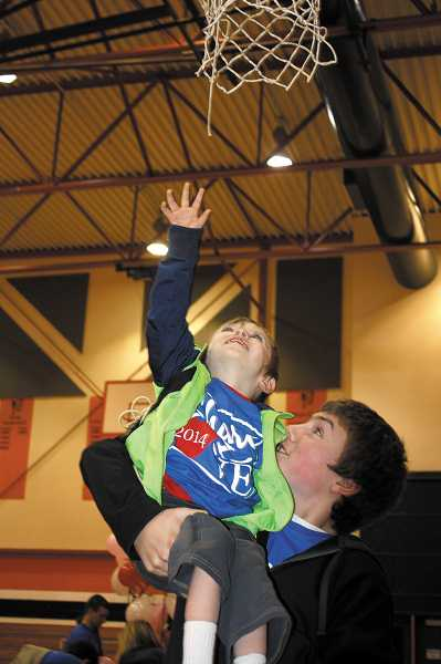 by: PEGGY SAVAGE - Jonathan Riehl helps little brother Naysen, 4, 'fly up to touch the basket in the MHS gym following the Share the Love assembly Friday.