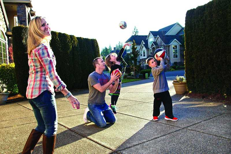 by: TIMES PHOTOS: JAIME VALDEZ - At home in Tualatin, Trail Blazers broadcaster Mike Barrett helps his daughter Gabby, 7, shoot a basket as his wife Shelly and son Jack, 8, observe her technique.