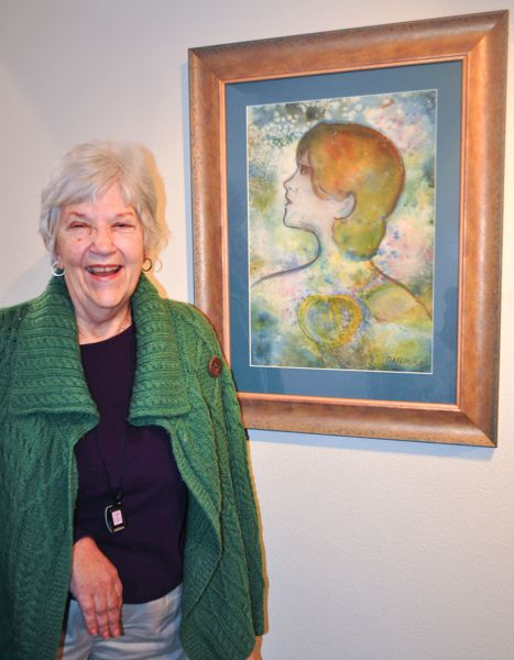 by: NEWS-TIMES PHOTO: MICHELLE THOMAS - Diane Glassmier, 76, stands in the lobby at The Beehive in Forest Grove next to one of her many paintings. The former professional violinist turned to watercolors after suffering a stroke at age 37.