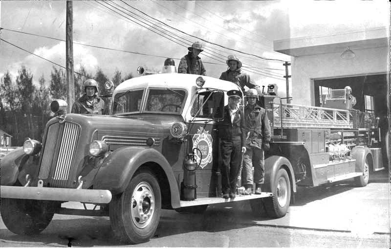 by: COURTESY PHOTO - Former fire marshal Marvin Wright, at left in this photo of an old Forest Grove Fire & Rescue ladder truck, served with the department in the 1960s. Back then Wright, now 72, was paid $400 a month.