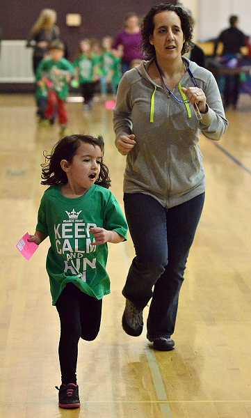 by: TIDINGS PHOTO: VERN UYETAKE - Kindergartener Elliot Ryder chalks up another lap with her mom, Stefanie Ryder, in the gym at Willamette Primary School Jan. 24.