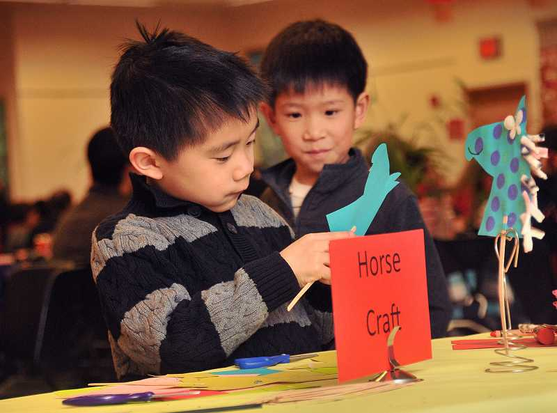 by: REVIEW PHOTO: VERN UYETAKE - Ethan Yipp, 7, works on a craft project as Egan Wong ,7, watches.