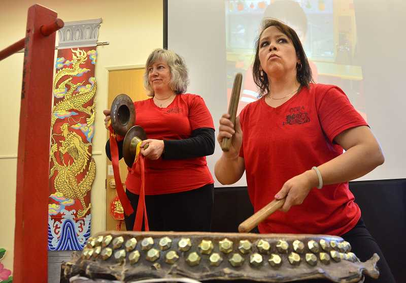 by: REVIEW PHOTO: VERN UYETAKE - Sue Anne Lee Reyes, right and Teya Burnham of International Lion Dance Team provide the beat for the Chinese Dragon performance.