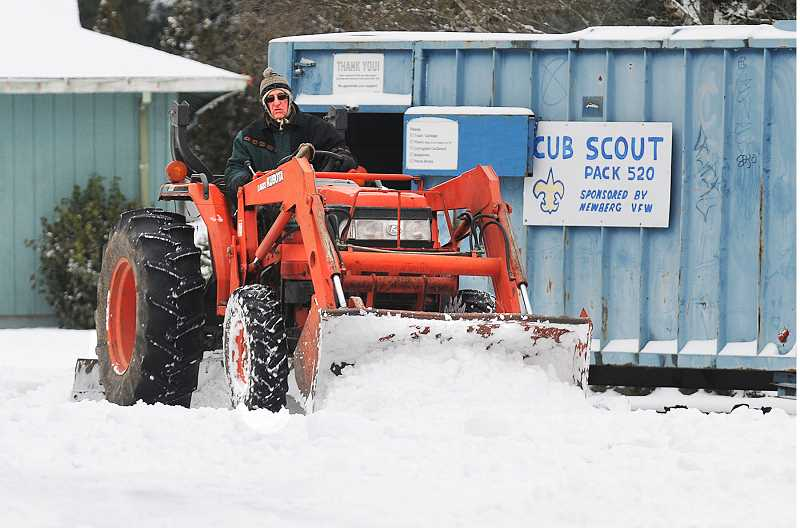 by: GARY ALLEN - A tractor operator plows snow in the parking lot at the Newberg Bi-Mart store.