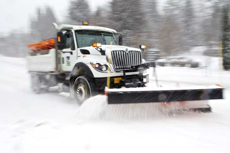 by: JAIME VALDEZ - A snow plow operated by Tigard Public Works employee Cale Brown clears snow along Southwest 68th Avenue in Tigard.