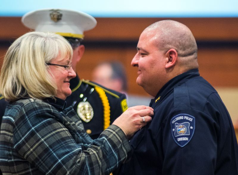 by: HILLSBORO TRIBUNE PHOTO: CHASE ALLGOOD - Susan Dobrowolski pins the police chiefs badge onto her husband Lee's uniform after he was sworn in as the Hillsboro Police Departments new chief Tuesday night.