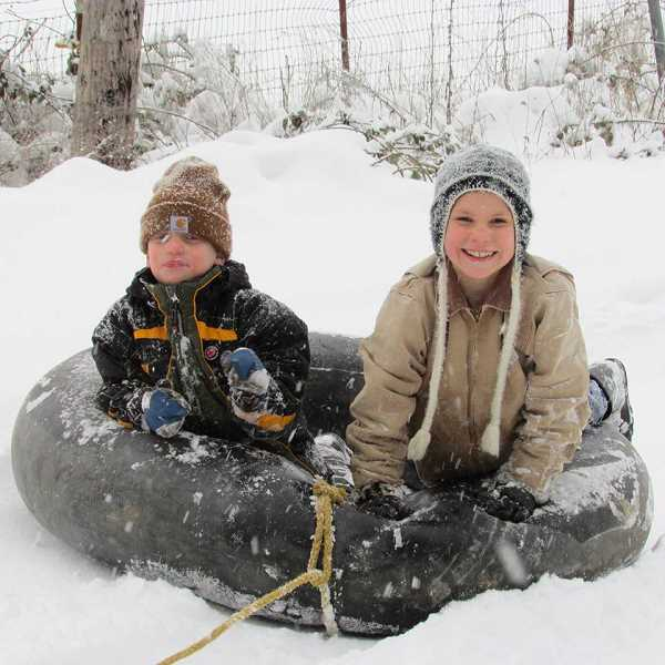 by: KAREN KIRSCH - Henry (left) and Charlie Kirsch experience the snowstorm from the comfort of an innertube on their farm in Donald.