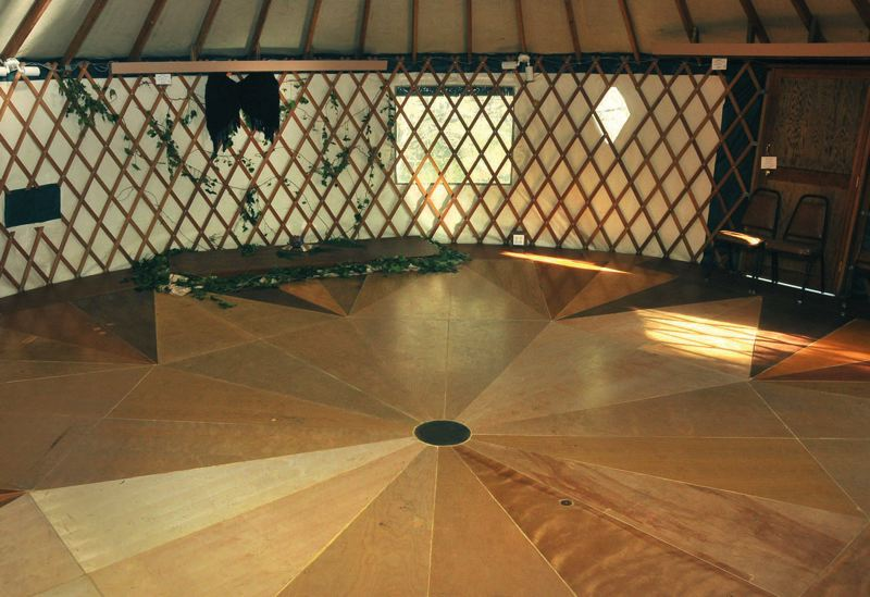by: PAMPLIN MEDIA GROUP: VERN UYETAKE - A bunch of old wooden doors were turned into an attractive floor for the yurt. Even more important, the yurt has a roof.