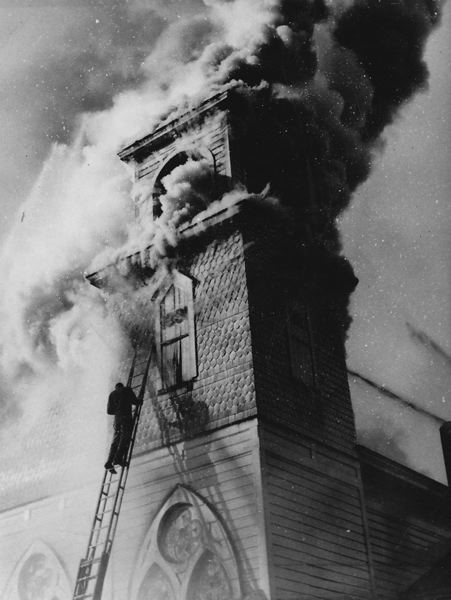 by: PHOTO COURTESY OF FOREST GROVE FIRE & RESCUE - A man unsuccessfully tries to save the church bell at First Christian Church during a 1948 fire.