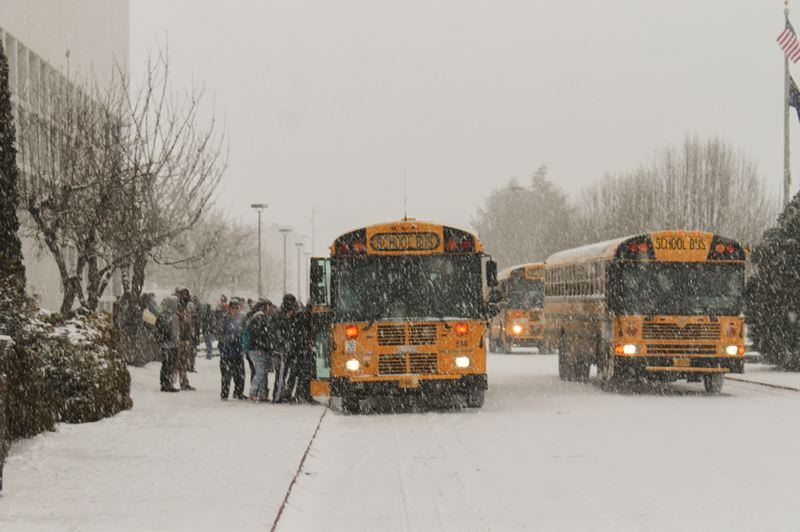 by: NEWS-TIMES PHOTO: JOHN SCHRAG - Buses at Forest Grove High School arrived early to pick up students last Thursday as snowfall caused classes to adjourn around mid-day.