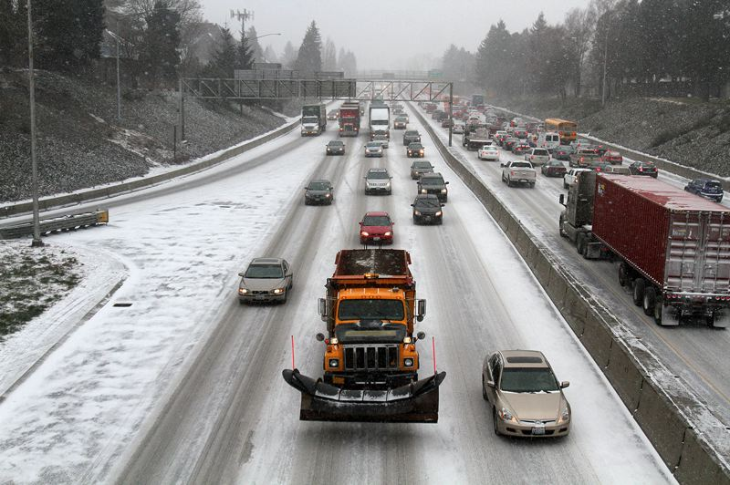 by: TRIBUNE PHOTO: JONATHAN HOUSE - An ODOT snow plow led the way in heavy traffic through North Portland Thursday, Feb. 6, hours after the snowstorm struck the region.