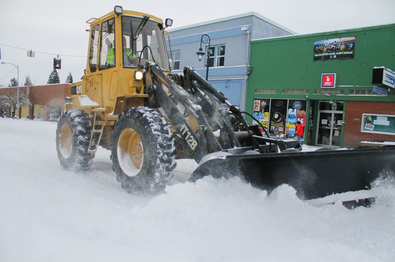 by: NEWS-TIMES PHOTO: JOHN SCHRAG - This tractor braved the streets last week when snow covered Forest Grove.