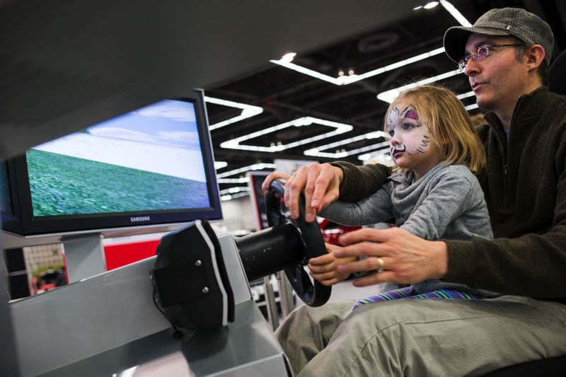 by: TRIBUNE PHOTO BY CHRIS ONSTOTT - James Ryan gives his daughter Elie, 3, a driving lesson at the simulator at the Toyota exhibit.