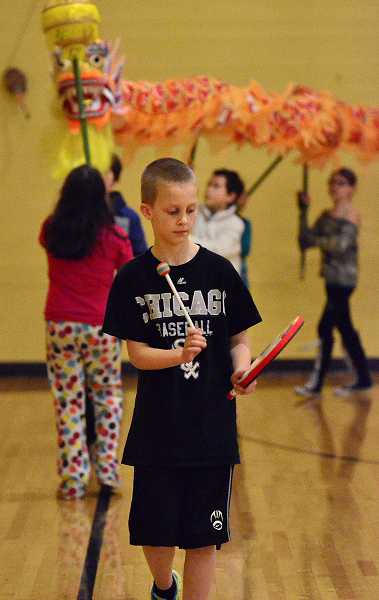 by: TIDINGS PHOTO: VERN UYETAKE - Cooper Hurley beats a drum to set the pace while he leads the schools new dragon on a parade to celebrate Chinese New Year.