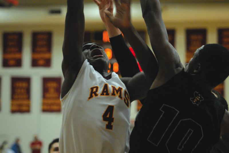 by: PAMPLIN MEDIA GROUP: DAVID BALL - Central Catholic's La'Mar Winston fights his way to the hoop during Tuesday's 53-43 win over Reynolds.