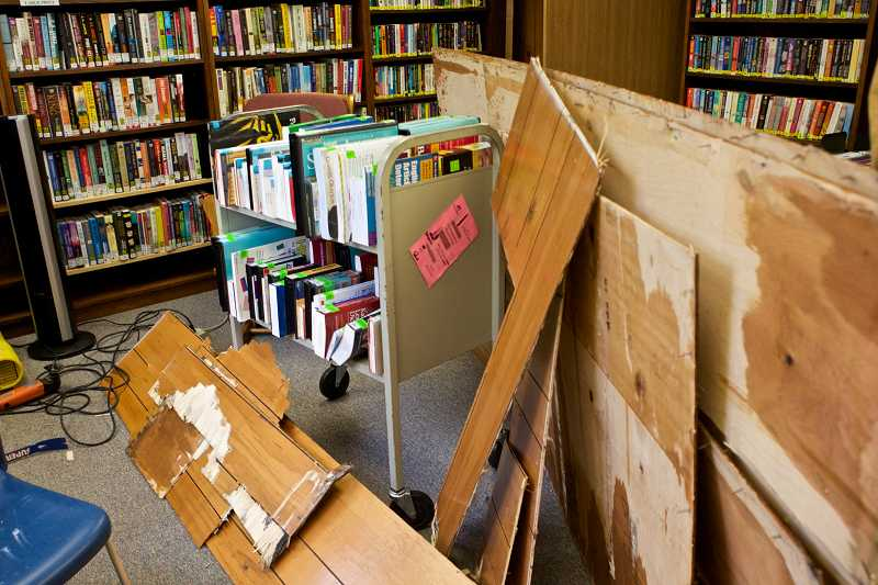 by: TIMES PHOTO: JAIME VALDEZ - Books sit in a dry space on a cart next to wood paneling that was removed by the staff at the West Slope Community Library.